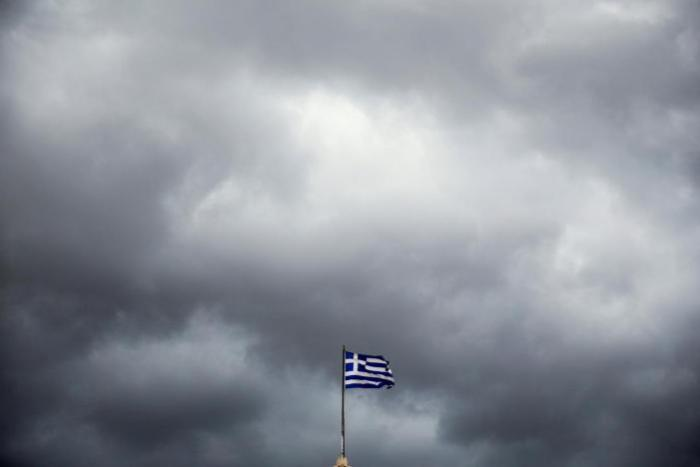 A Greek national flag flutters atop Athens University